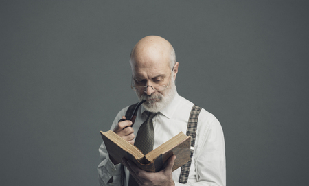 Confident senior professor smoking a pipe and reading an old book: knowledge and education concept Standard-Bild - 116681610