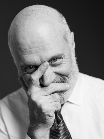 Mature man posing with a hand on his face and looking at camera Standard-Bild - 116681612