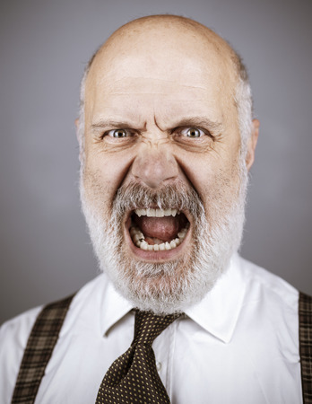 Angry mature man posing and shouting at the camera, he is aggressive and threatening Standard-Bild - 116681617