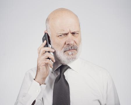 Suspicious senior man having a phone call and having hearing loss problems Standard-Bild - 116681620