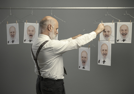 Mature businessman staring at his different personalities on a collection of hanging portraits and making a comparison: mind self analysis and emotions concept Standard-Bild - 116681622