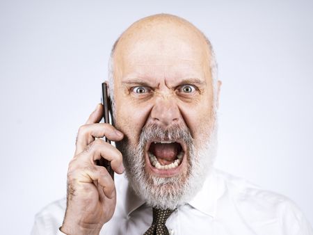 Angry furious mid age businessman having a phone call with his smartphone Standard-Bild - 116681624