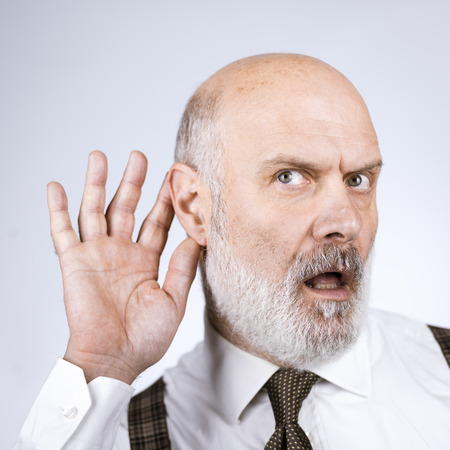 Senior businessman keeping a hand next to his ear and overhearing something, he has hearing loss problems