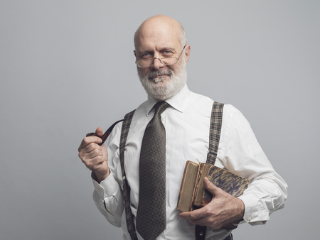 Smiling senior academic professor smoking a pipe and posing Standard-Bild - 116681555