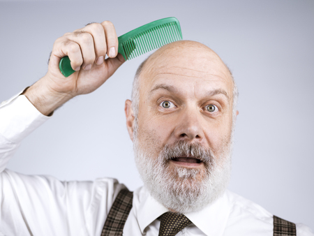 Funny senior bald man combing his head and smiling at camera Standard-Bild - 116681561