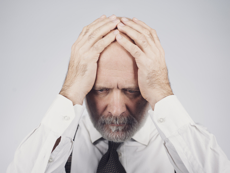 Desperate mature man with head in hands: he is feeling depressed, exhausted and hopeless