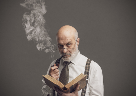 Confident senior professor smoking a pipe and reading an old book, knowledge and education concept
