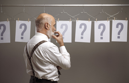 Pensive man comparing different possibilities and questions, he is staring at many question marks Imagens