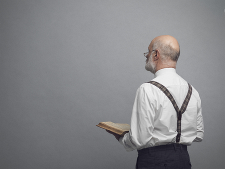 Senior academic professor holding a book and teaching, he is staring at the blackboard