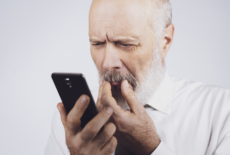 Senior man using apps on the smartphone, he is having difficulties and vision problems 版權商用圖片