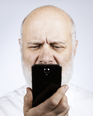 Senior man using apps on the smartphone, he is having difficulties and vision problems Standard-Bild - 116701807