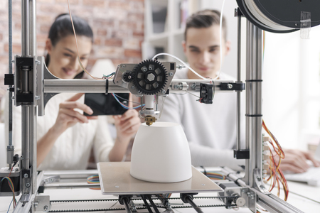 Engineering students printing prototype models using a 3D printer, the girl is taking pictures with a smartphone and sharing online Stock Photo
