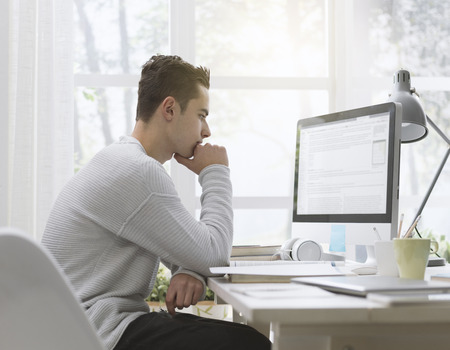 Smart college student using computer at home, he is studying and connecting online Standard-Bild - 116702131