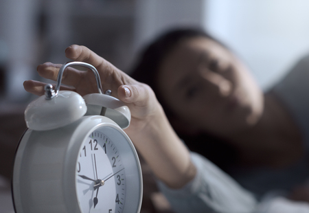 Woman waking up in the morning in her bed and turning off the alarm clock