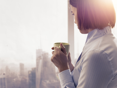 Businesswoman standing in front of a window and having a relaxing coffee break, she is holding a cup