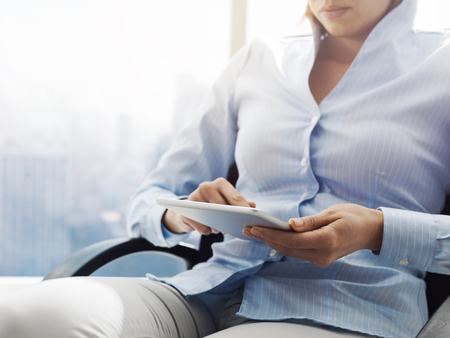 Professional businesswoman sitting on a office chair and connecting online using a digital touch screen tablet, business and communication concept