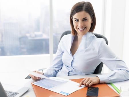 Smiling young businesswoman sitting at office desk and reviewing financial reports, accounting and business management concept Stock Photo