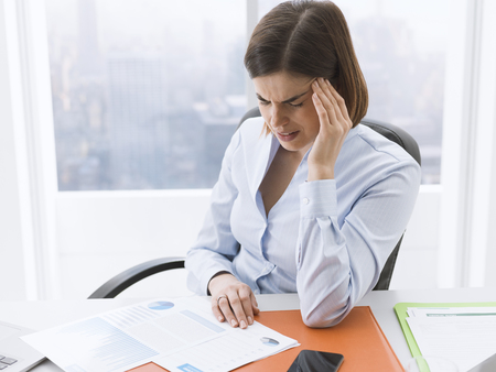 Stressed tired businesswoman sitting at office desk and having a bad headache, she is touching her temple Stock Photo