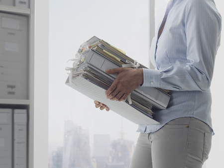 Female office worker carrying folders and files in the archive, administration and business concept Stock Photo