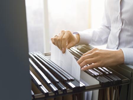 Impiegata d'ufficio professionale femminile che cerca file e scartoffie nello schedario