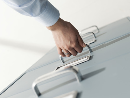 Professional secretary working and searching files in the archive, she is opening a filing cabinets drawer Stock Photo