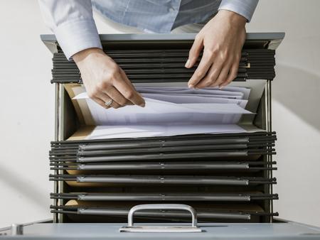 Impiegata femminile che cerca file e scartoffie nell'archivio, sta controllando le cartelle in uno schedario Archivio Fotografico