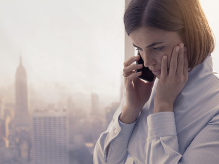 Business woman receiving bad news on the phone, she is concerned and worried