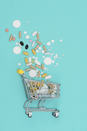 Miniature shopping cart filled with pills, tablets and capsules: pharmacy shopping, medicine and drug abuse concept Stockfoto