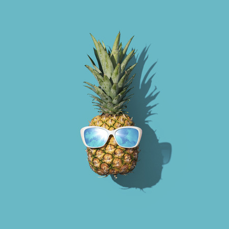 Funny fresh pineapple wearing sunglasses, summer fun concept Imagens