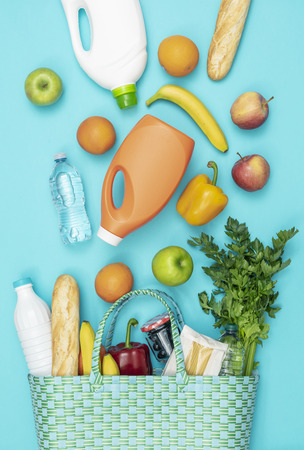 Fresh vegetables and grocery products falling into a reusable shopping bag