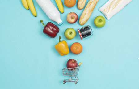 Fresh products falling into a miniature shopping cart, grocery shopping on a budget concept