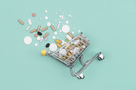Miniature shopping cart filled with pills, tablets and capsules: pharmacy shopping, medicine and drug abuse concept Archivio Fotografico