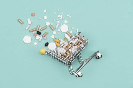 Panier d'achat miniature rempli de pilules, de comprimés et de capsules : concept d'achat de pharmacie, de médicaments et de toxicomanie Banque d'images