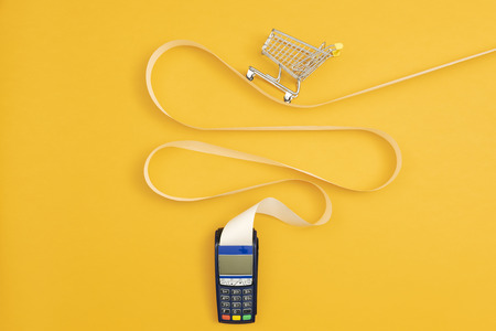 Panier vide miniature sur un long reçu de terminal de point de vente, concept d'achat coûteux