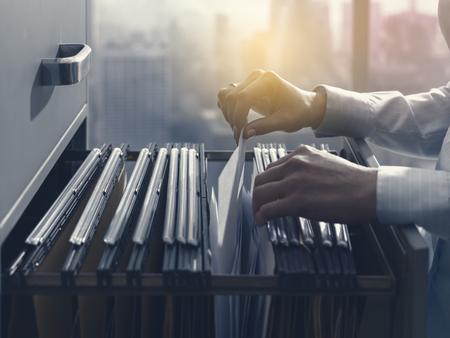 Profesjonalna urzędniczka biurowa przeszukująca akta i dokumenty w szafce na dokumenty
