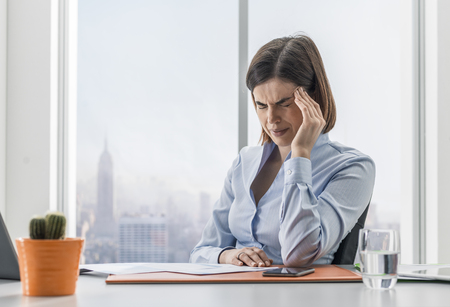 Stressed tired businesswoman sitting at office desk and having a bad headache, she is touching her temple Stock fotó