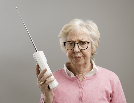 Frustrated senior woman using an old cordless telephone, she is looking at camera disappointed