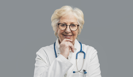 Senior confident female doctor posing with hand on chin on gray background and smiling at camera Reklamní fotografie