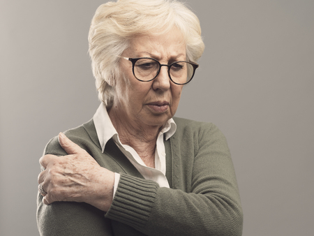 Sad senior lady with arm and joint pain, healthcare and rheumatism concept