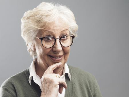 Sonriente mujer mayor pensando con la mano en la barbilla, concepto de oportunidad y soluciones