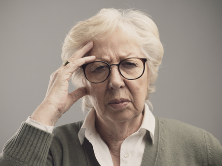 Old woman having a bad headache, she is touching her forehead and feeling sick Stock Photo