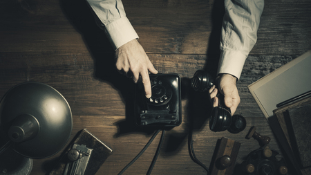 Businessman making a phone call late at night with a rotary dial telephone in a vintage office, flat lay desktop Imagens