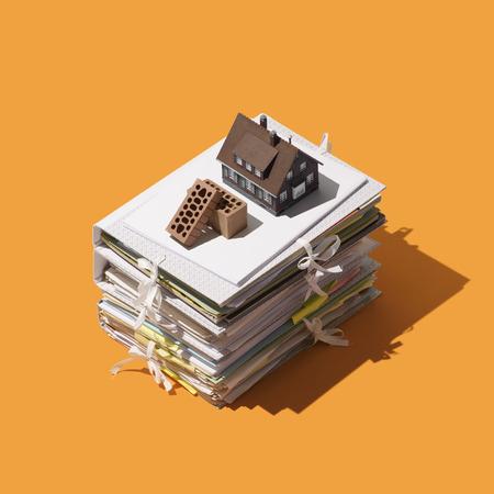 Home construction and real estate: pile of paperwork, bricks and model house Reklamní fotografie