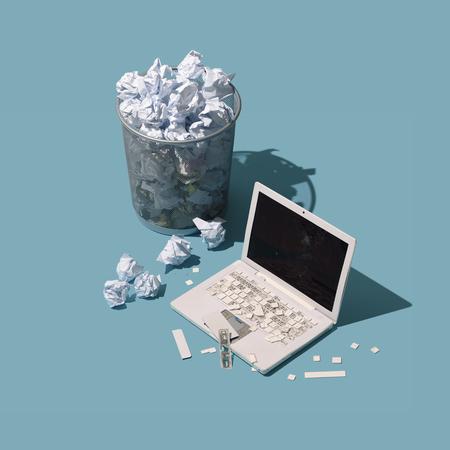 Zerstörter Laptop und zerknittertes Papier: Überarbeitung und Frustrationskonzept