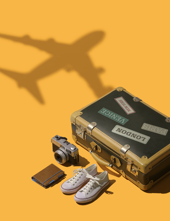 Getting ready to leave for summer vacations: suitcase and airplane leaving, travel and tourism concept