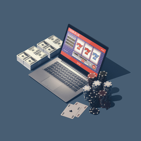 Online casino games, slots and gambling: laptop with slot machine app, piles of chips and packs of dollars, winning and leisure concept 版權商用圖片