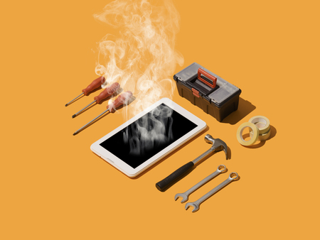 Phone and digital devices repair service, smoking overheating broken phone and DIY tools Stock Photo