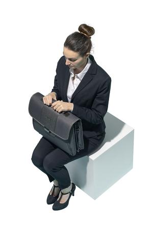 Corporate businesswoman sitting and waiting on white background Standard-Bild - 124477648