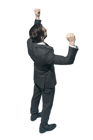 Cheerful winner businessman celebrating his success with fists raised on white background