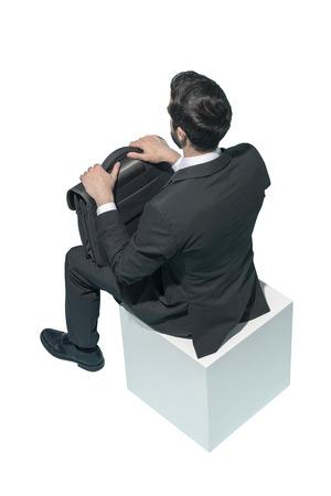 Corporate businessman sitting and waiting on white background Standard-Bild - 124477655